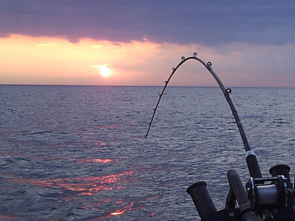 sunset on ocean with a fishing rod and reel